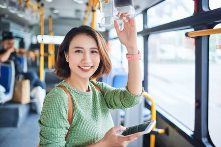 Beautiful young asian woman who see a smart phone in city bus 版權商用圖片