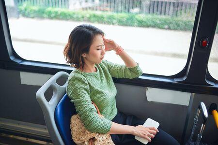 Femme asiatique se sentant fatiguée par des maux de tête lors d'un voyage en bus Banque d'images
