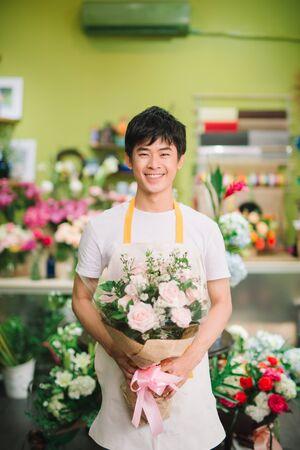Blumenladen bei Tageslicht. Mann, der schönen Blumenstrauß hält.