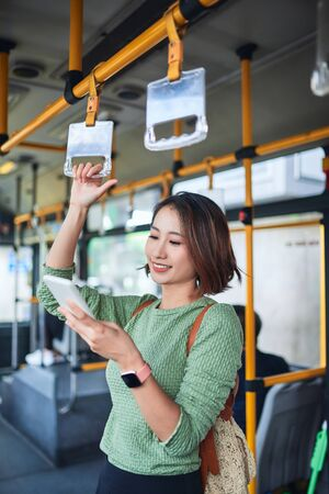 Beautiful young woman standing in city bus and talking on mobile phone. 免版税图像