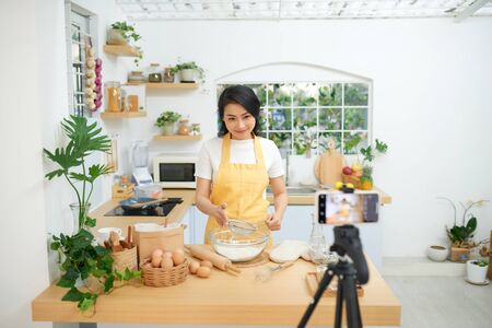 Young asian woman recording video for her blog