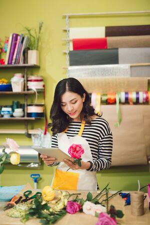 Lächelnde junge Floristin, die in ihrem Blumenladen steht und ihr Inventar mit einem digitalen Tablet überprüft