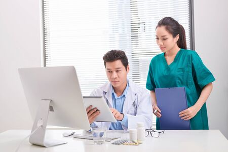 Two medical doctors consulting, smiling at office desk Imagens
