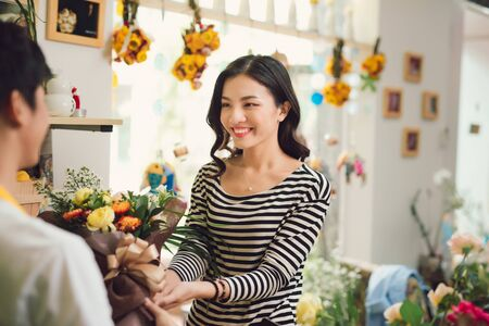 Florist giving bouquet of flower to woman in flower shop 版權商用圖片