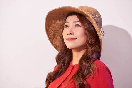 Blissful lady with broad smile posing in sunny day. Laughing girl in red clothes and trendy straw hat enjoying good weather in weekend.