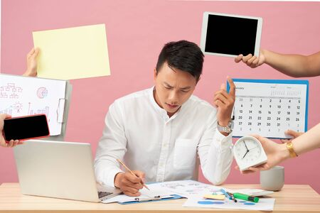 Sad young man sits at desktop, hands with papers, alarm clock, touchpad, notepad with stickers, studies documentation, isolated over pink background