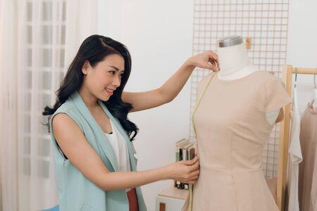 Una ragazza asiatica sta lavorando nello studio dell'officina. Si adatta al vestito sul manichino. Archivio Fotografico