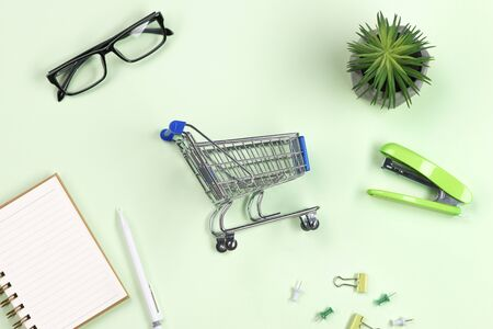 shopping online concept. small blue trolley and office supplies on green background Stock Photo