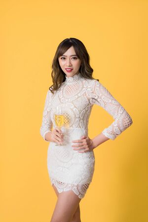 Happy face of luxurious Asian girl smiling to camera with a glass of champagne, isolated on yellow background Stock Photo