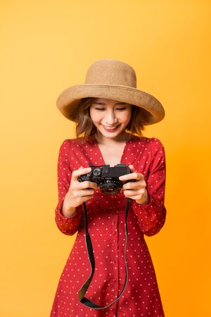 Happy Asian girl checking photos on her camera while wearing red dress and hat isolated on orange background.