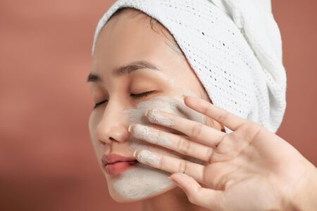 Beautiful cheerful Asian teen girl applying facial clay mask. Beauty treatments, isolated on light background. Stock Photo