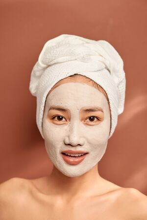 Close-up portrait of attractive girl with a towel on head and clay mask on face isolated over orange background.