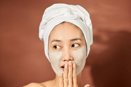 Beautiful woman with clay facial mask over orange background. Beauty treatment and spa concept. Stock Photo