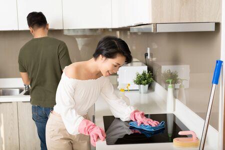 Jeune couple asiatique nettoyant la cuisine et s'amusant. Concept de nettoyage et d'hygiène à domicile