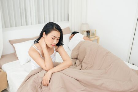 Unhappy Young Couple Sitting On Bed In Bedroom