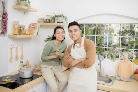 Happy young couple eating and talking in the kitchen