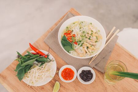 Pho Bo - Vietnamese fresh rice noodle soup with beef, herbs and chili. Stock being poured. Vietnams national dish.
