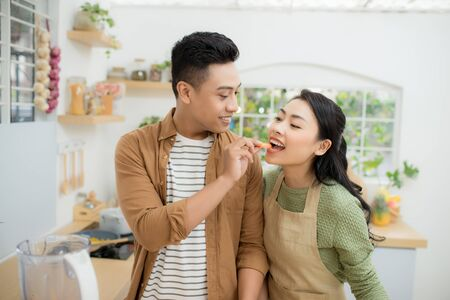 Beautiful happy asian couple are feeding each other in the kitchen.
