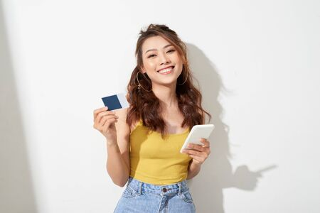 Asian young woman holding a card and mobile phone 免版税图像