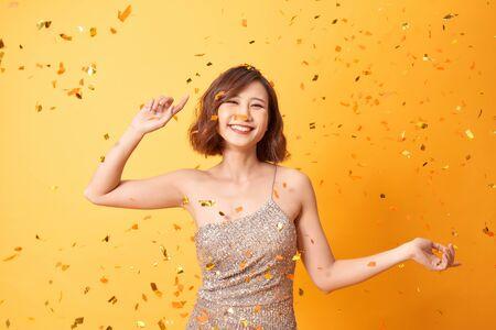 Junge Frau tanzt zu Hause unter Konfetti und feiert Geburtstag