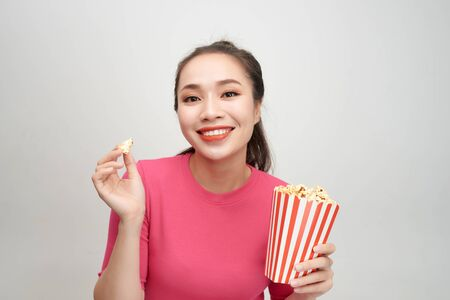 Portrait of a cheery pretty girl eating popcorn isolated over white background