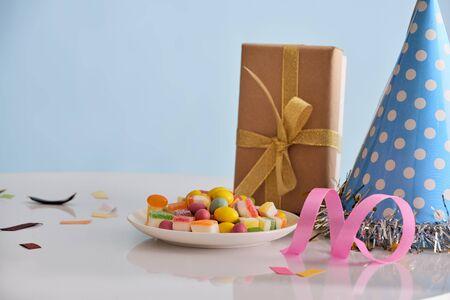 Geburtstagsfeierhintergrund mit Cupcake, Partyhut und Geschenk