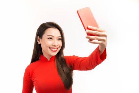 Jeune femme asiatique en rouge ao dai prendre le selfie