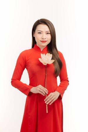 Beauty Vietnamese women wear traditional dress with lotus flower in her hand 写真素材