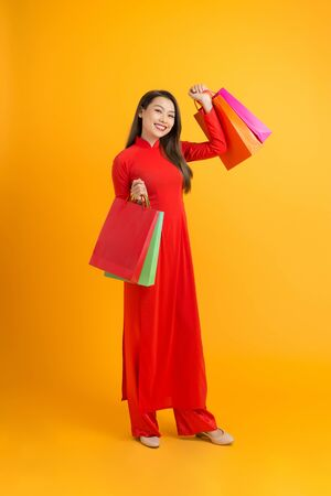 Young Asian female in traditional ao dai dress shopping, hand holding paper bag, celebrating Lunar New Year or spring festival