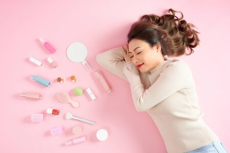 Sleeping Asian woman lying on pink background with her cosmetics. Top view
