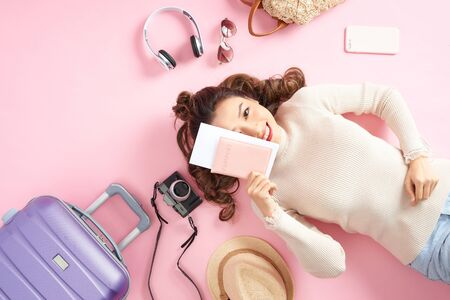 Asian woman holding her passport and lying surround her travel luggage on pink floor. Top view