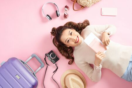 Young Asian woman showing her passport while lying on pink floor with travel luggage surround. Top view Banco de Imagens