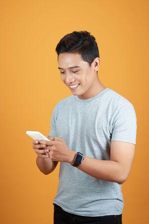 Smart casual asian man using smartphone in orange background.