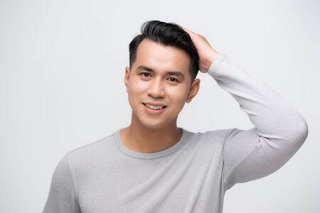 Asian man looking at his hair in mirror Imagens