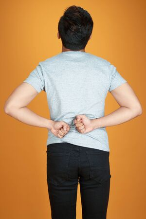 Men with low back pain on a color orange background  medical and health concepts.
