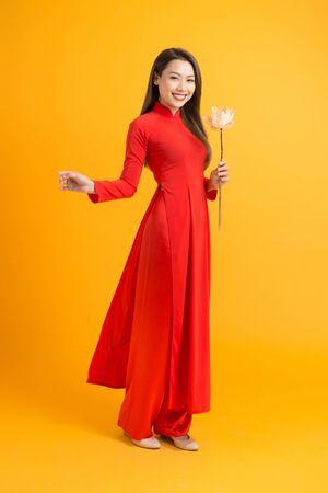 Asian beauty woman. Beautiful happy Vietnamese girl wearing national traditional red ao dai dress