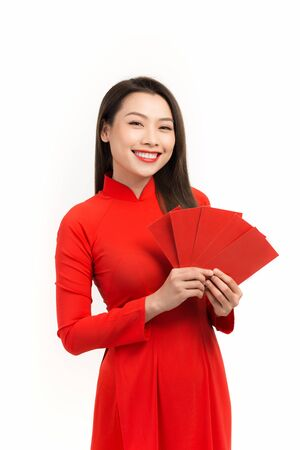 Young asian woman holds red envelopes for Lunar New Year. She is happy because she gets many red envelopes from her family