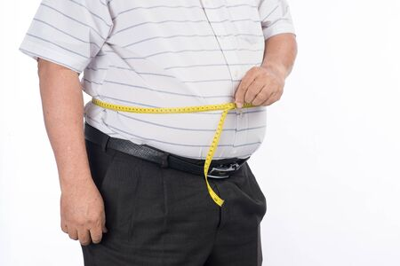 Fat mature man measuring his belly with measurement tape, isolated on white background 免版税图像