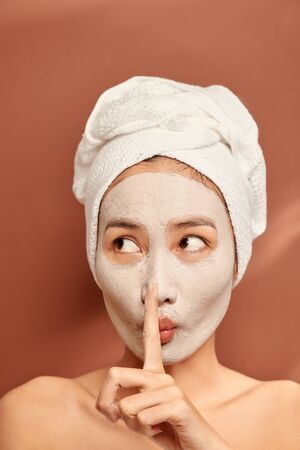 Beautiful woman with clay facial mask over orange background. Beauty treatment and spa concept.