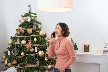 Mujer joven llamar al teléfono móvil por el árbol de Navidad
