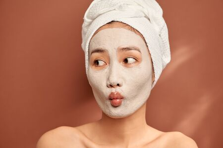 Spa girl with pleased facial expression, applies clay mask on face, gets beauty treatments, wears white soft towel on head Stock fotó