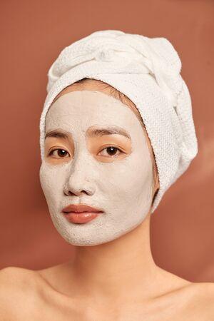 Portret van een jonge Aziatische vrouw op een oranje achtergrond met een kleimasker op haar gezicht en een handdoek op haar hoofd die lacht.