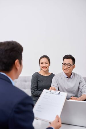 Happy young couple hold each otherâ??s hands listening to female agent, planning wedding, consulting investment advisor, hearing good news, casual marriage registration, buying real estate