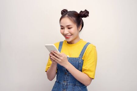 Attractive young asian woman using her cell phone to send a text message