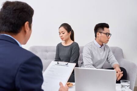 Young angry couple of cheated investors holding papers arguing with male real estate agent, defrauded property purchasers protecting their rights, too high interest rate of banking loan or mortgage