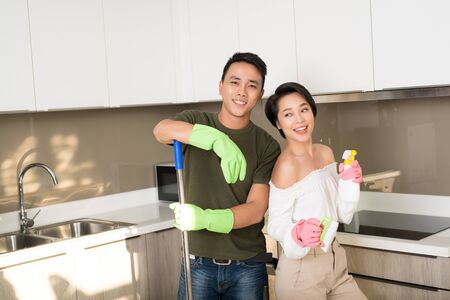 Joven pareja asiática feliz se divierte mientras hace la limpieza en casa.
