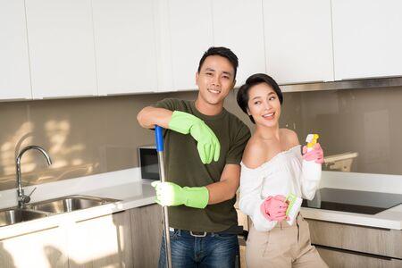 La giovane coppia asiatica felice si diverte mentre fa le pulizie a casa.