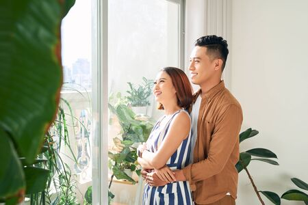 Happy young Asian couple looking through window at home Imagens