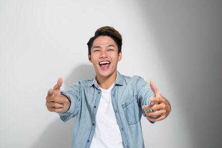 Asiatische fröhliche aufgeregte Männerfreunde tragen Jeans-T-Shirt, die isoliert auf weißem Hintergrund stehen und Daumen nach oben zeigen Standard-Bild