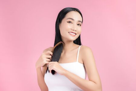 Close up portrait of happy satisfied beautiful girl while combing her hair 版權商用圖片